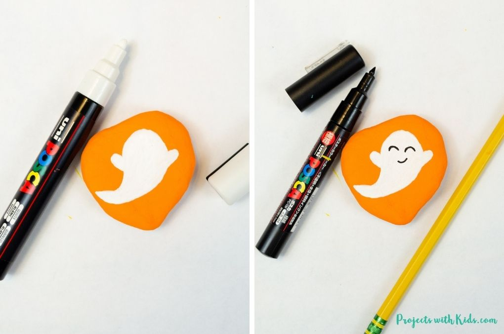 Painting a ghost and drawing on a face with paint pens for a ghost painted Halloween rock painting idea.