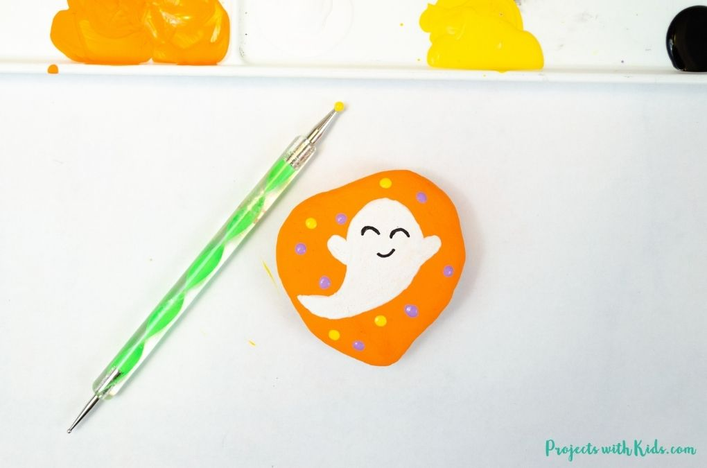 using a dotting tool to paint dots on a painted rock