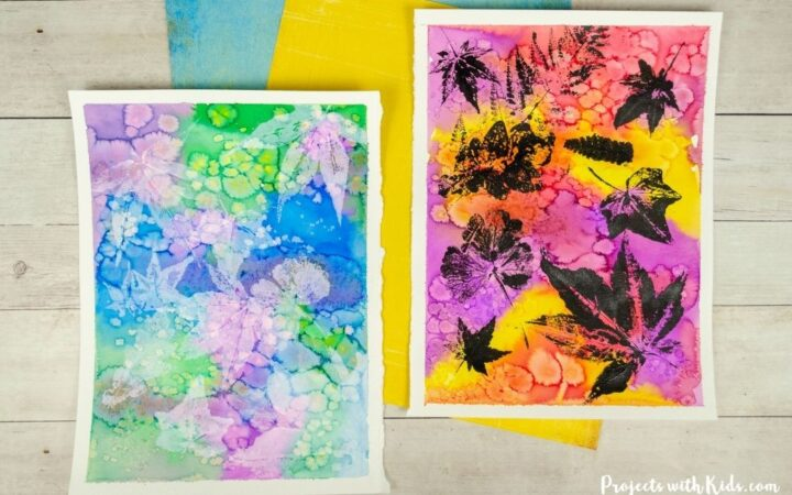 Leaf printing art with colorful watercolor background and black and white printed leaves.