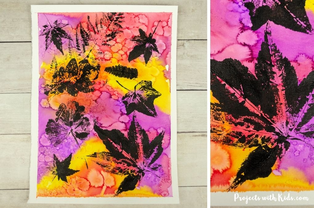 Watercolor background with black acrylic printed leaves.