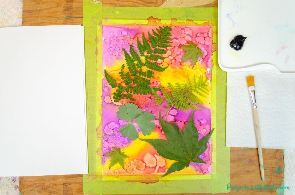 real leaves placed on top of a watercolor painting.
