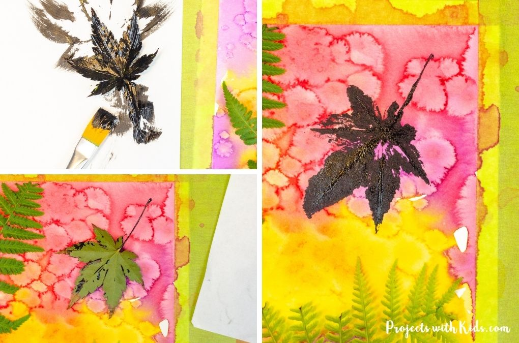 printing a leaf onto a watercolor painted background with black paint.