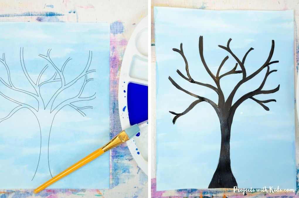 Painting a sky with blue watercolor paint and painting a tree with black acrylic paint.