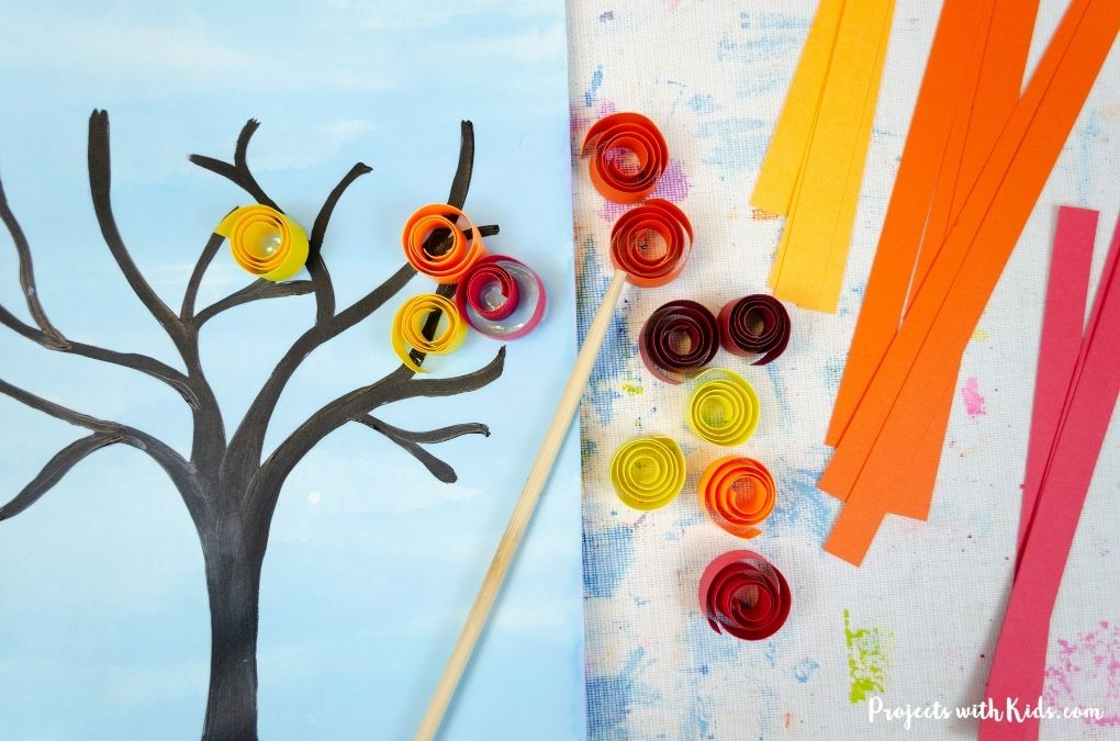 Glueing paper quills to a tree painting
